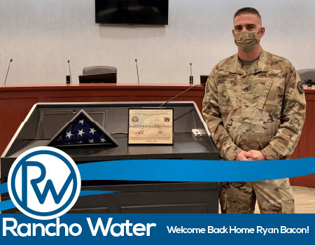 Photo of Ryan Bacon next to a flag in a case and a certificate to Rancho Water
